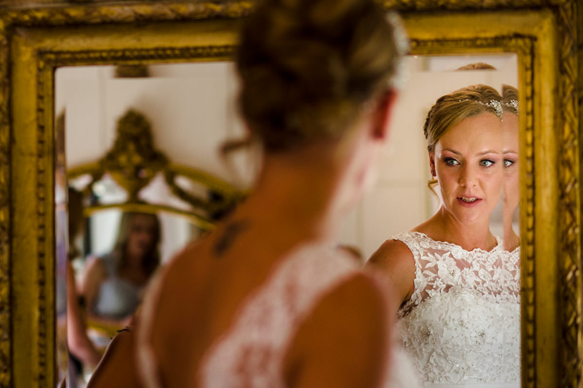 Blond bride in wedding dress looks in the mirror