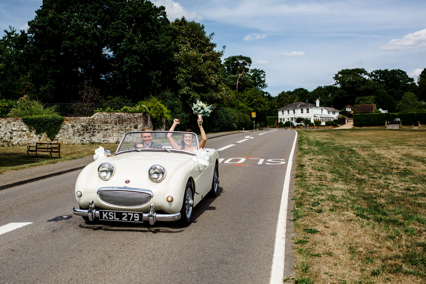 A Ramster Hall wedding photographer captures a just married couple driving their car