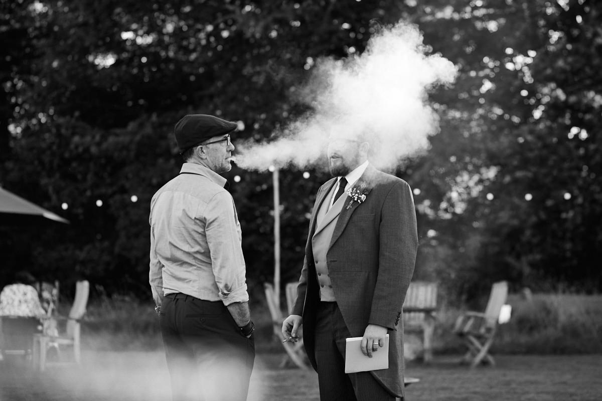 Funny wedding photo of a man blowing his vape smoke