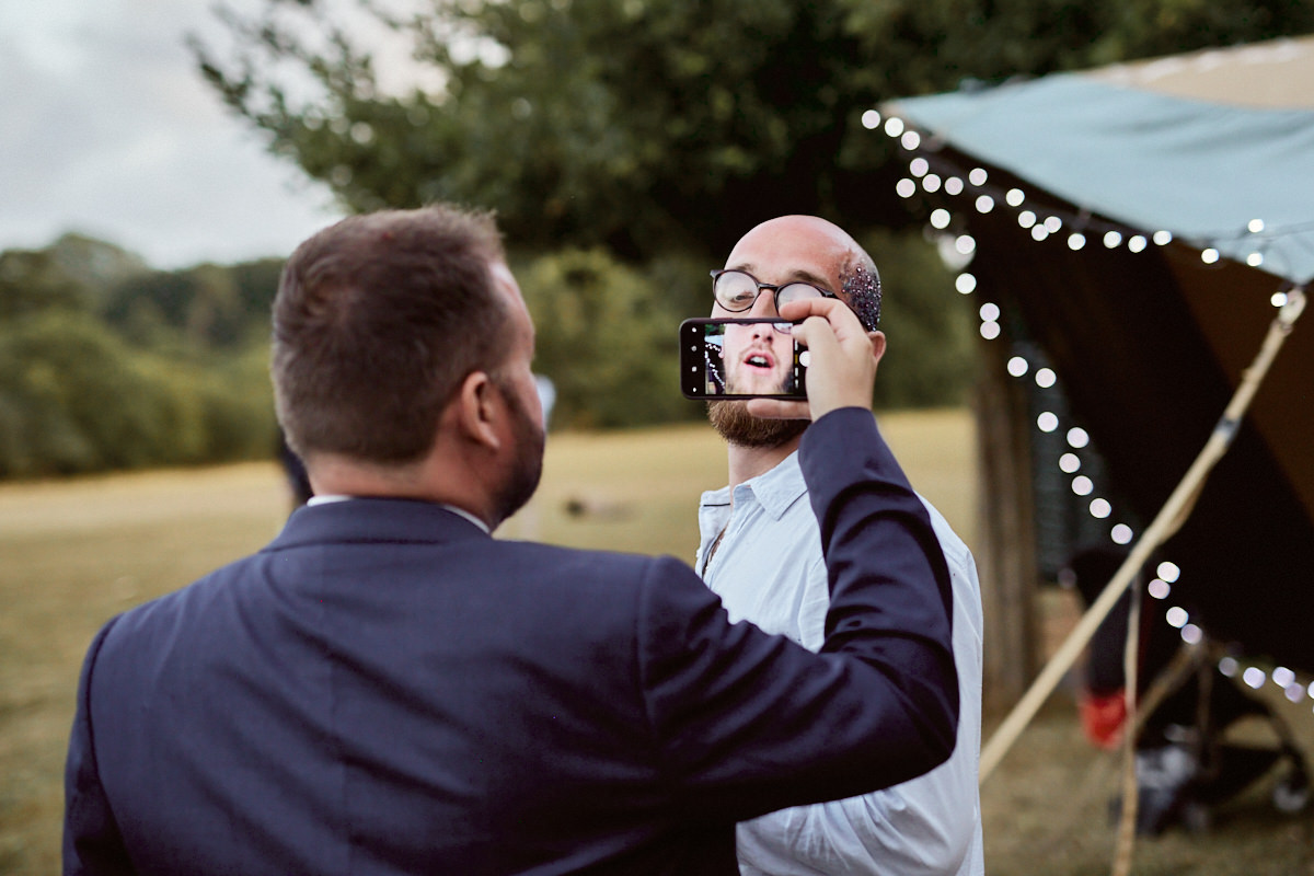 Funny wedding photo of a guest having picture taken on mobile phone