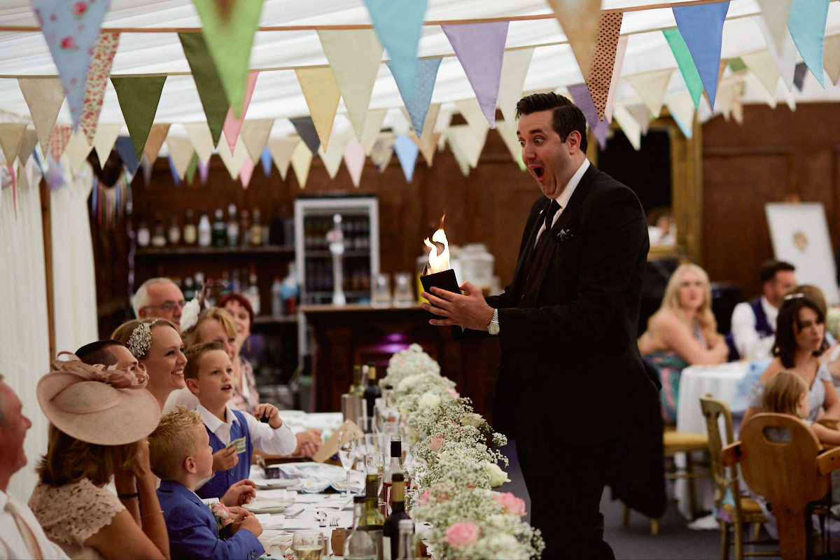 Funny wedding photo of magician Alexander James setting fire to his wallet at Broyle Place