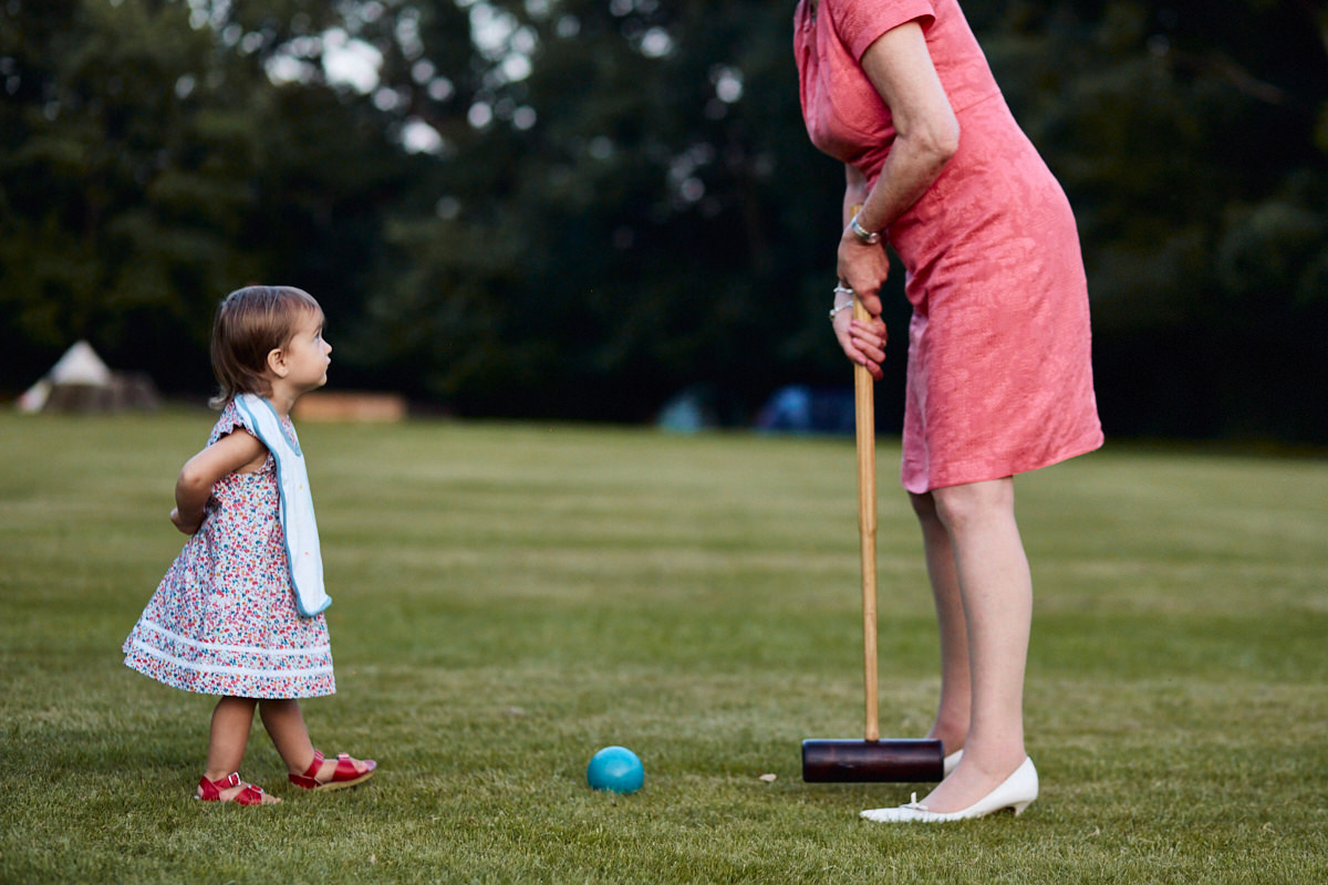 Funny wedding photo a girl playing croquet with a guest