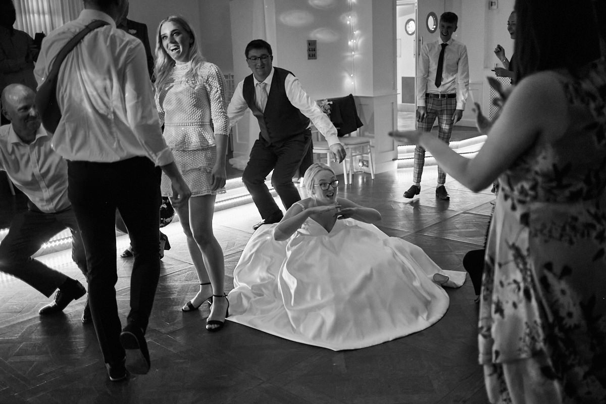 Funny wedding photo of bride dancing in her dress