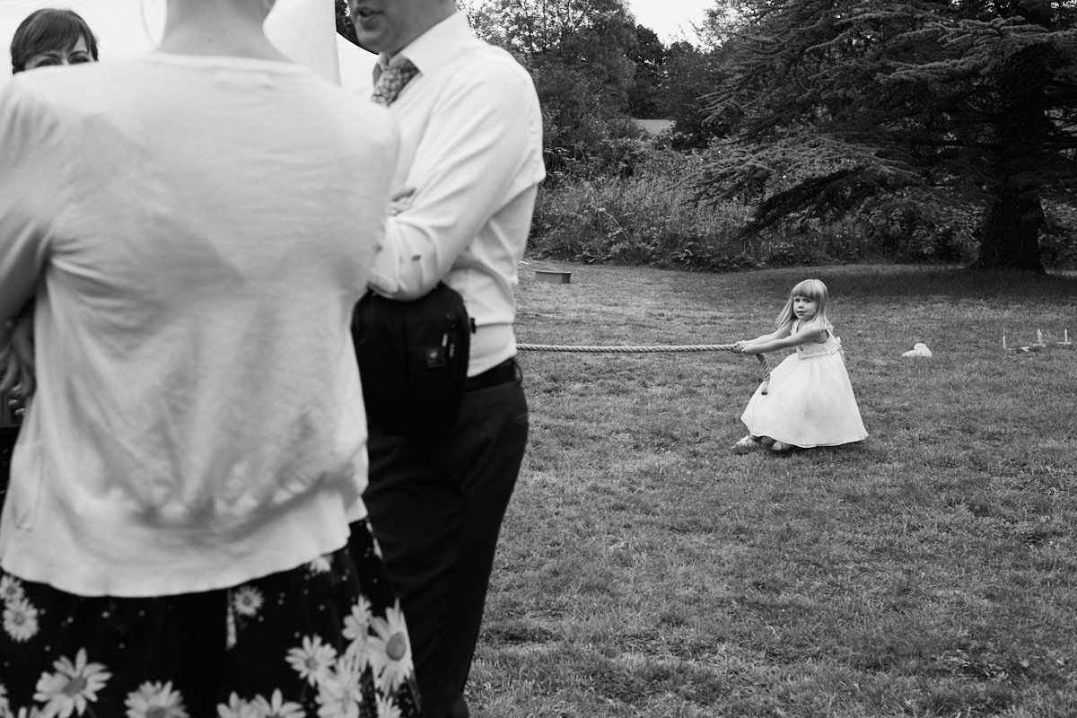 Funny wedding photo of a girl pulling on a rope at Bore Place