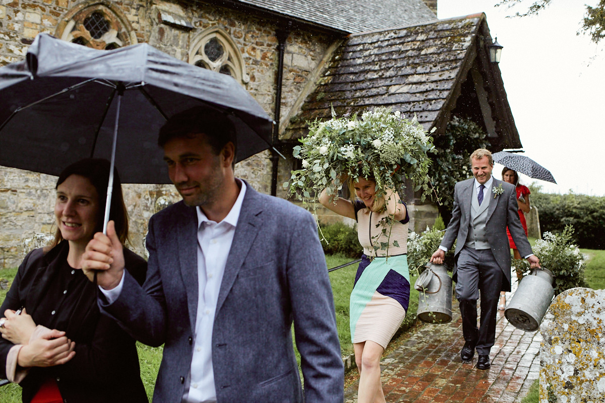 Funny wedding photo of a wedding guest sheltering from rain under a plant