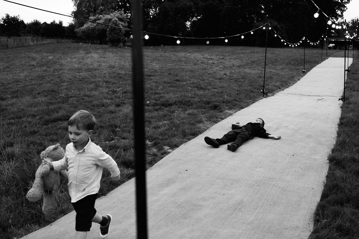 Funny wedding photo of a boy running away with a teddy bear