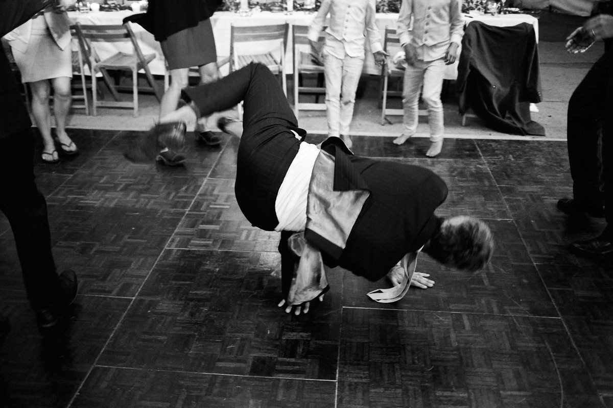 Funny wedding photo of a man in a suit breakdancing
