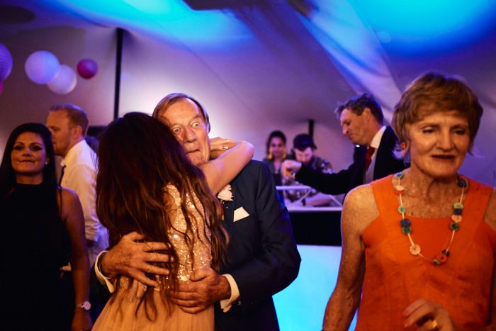 Funny wedding photo of a man dancing a pulling surprising face
