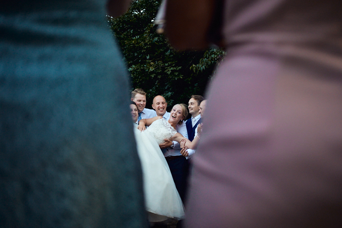 Funny wedding photo of a bride being carried by the groomsmen