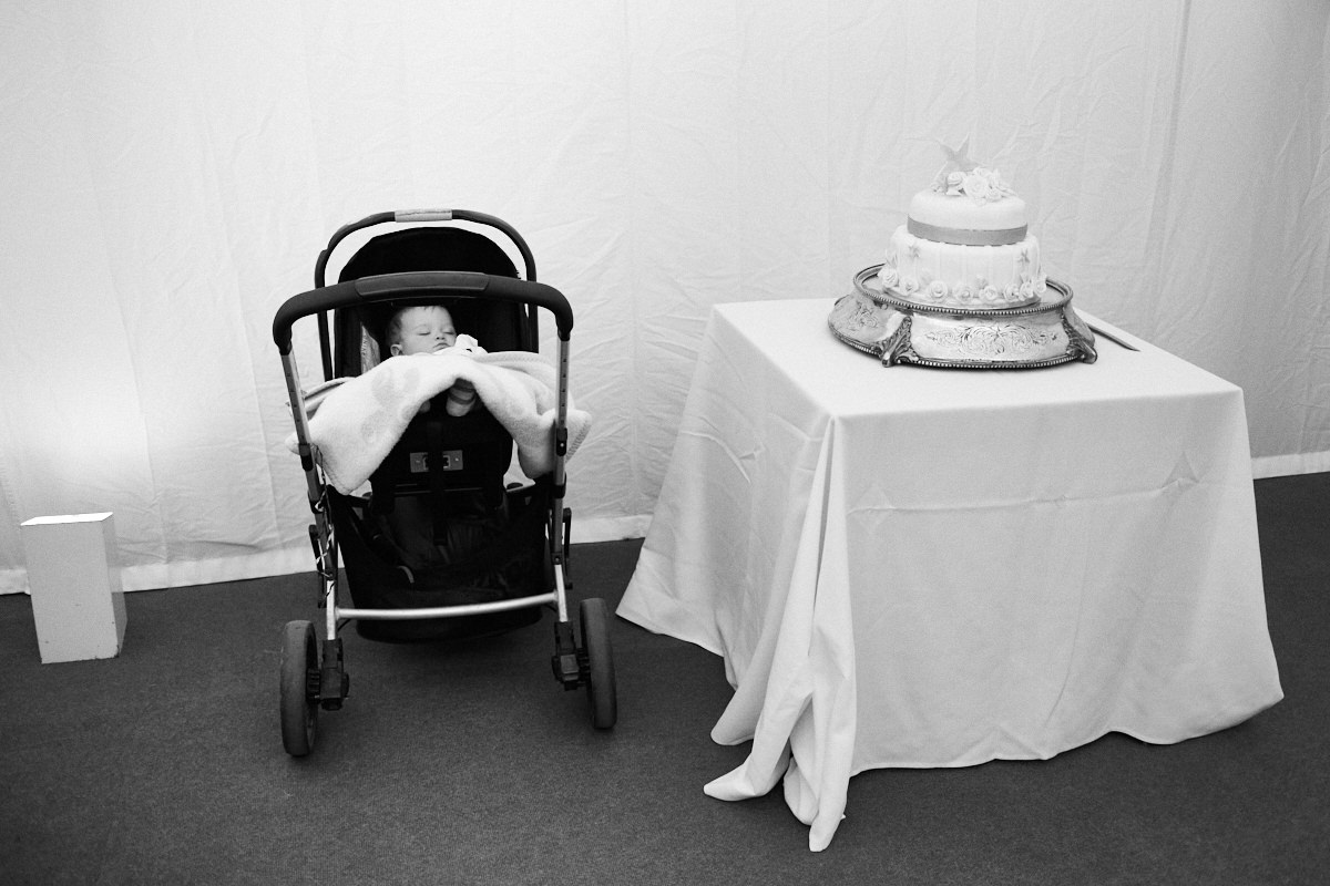 Funny wedding photo of a sleeping baby next to a large wedding cake