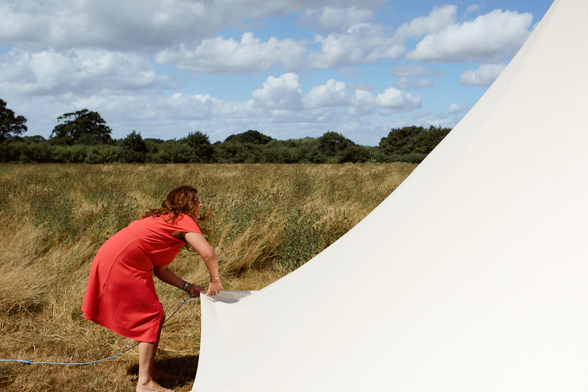 Funny wedding photo of woman putting up a bell tent