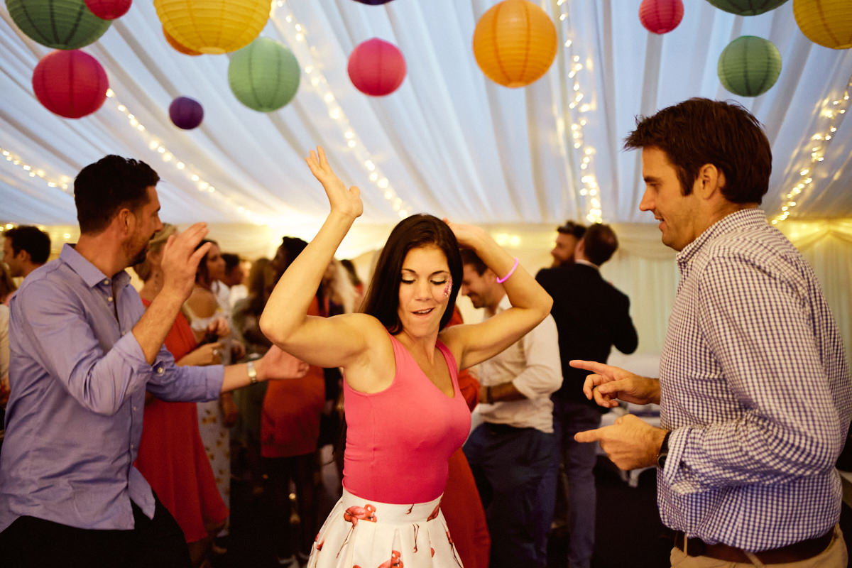 Funny wedding photo of a woman and man dancing in a marquee