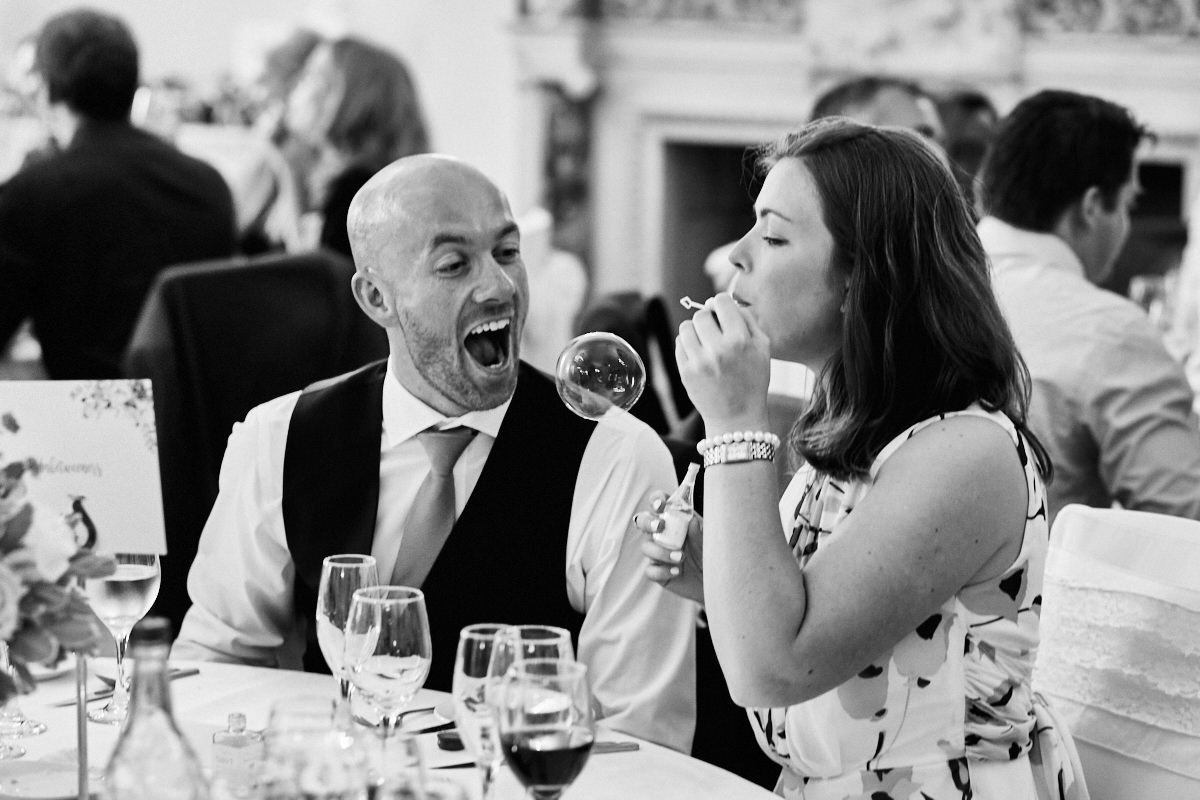 Funny wedding photo of a man about to eat a bubble