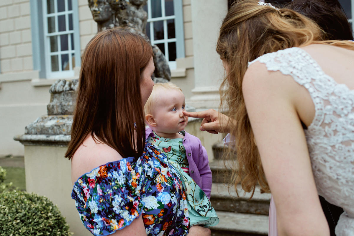 Funny wedding photo of a baby with a finger on her nose