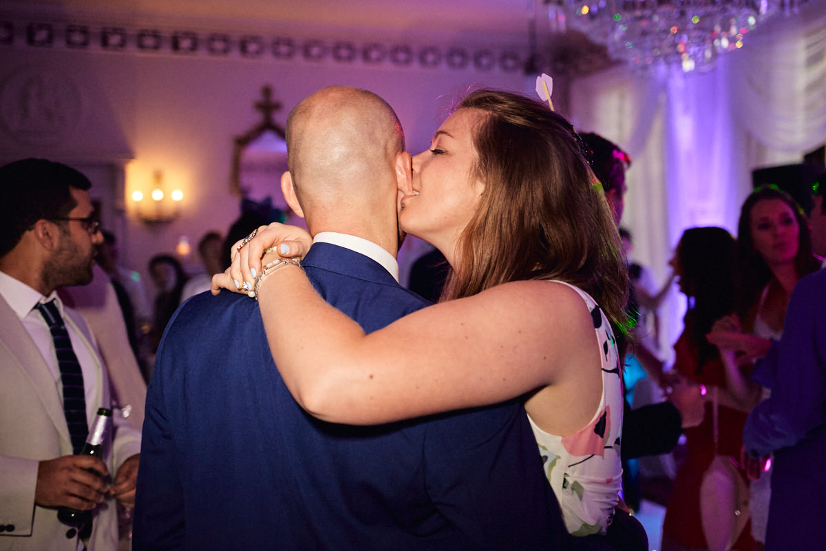 Funny wedding photo of a guest nibbling her boyfriend's ear