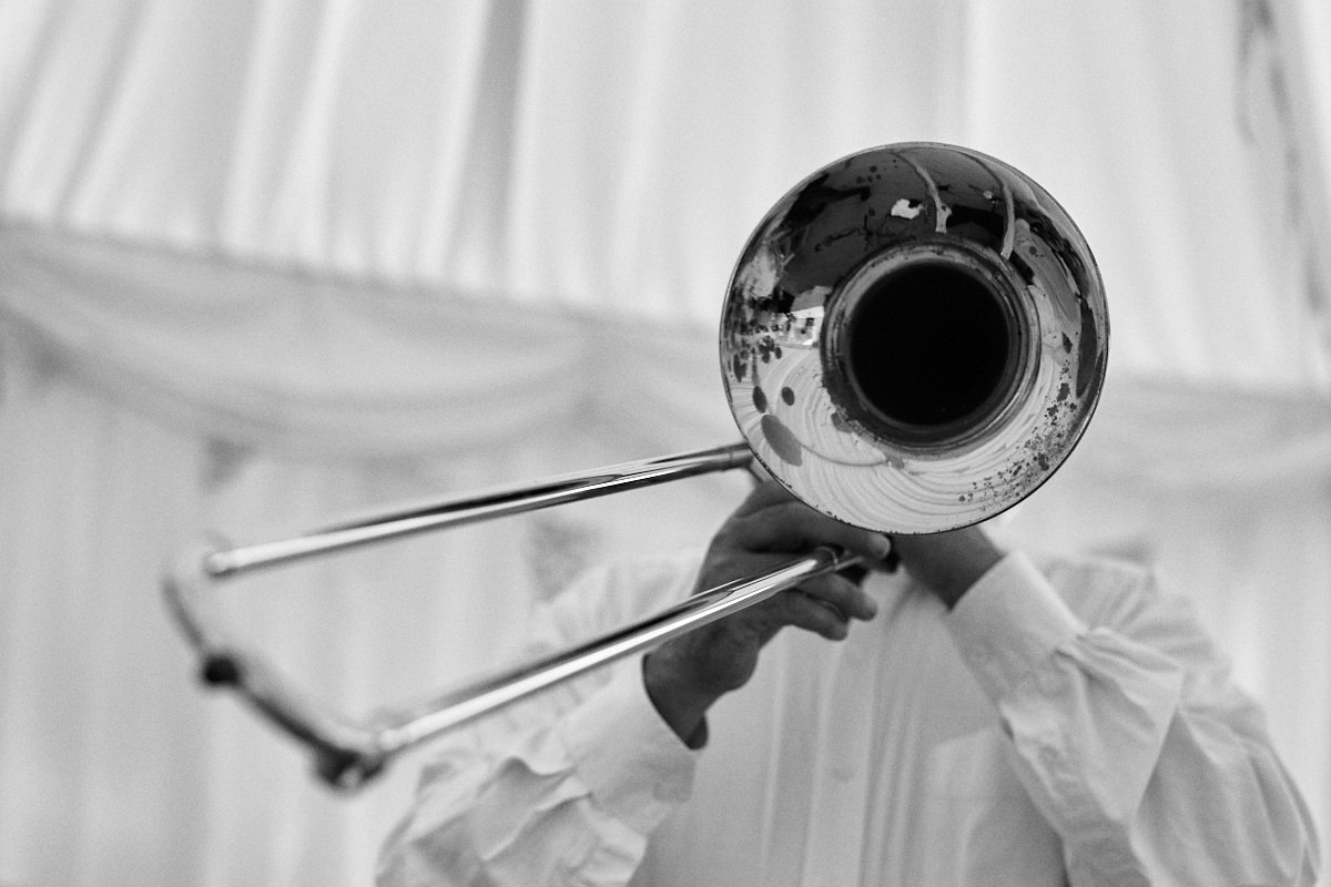 Funny wedding photo of a man playing a trumpet