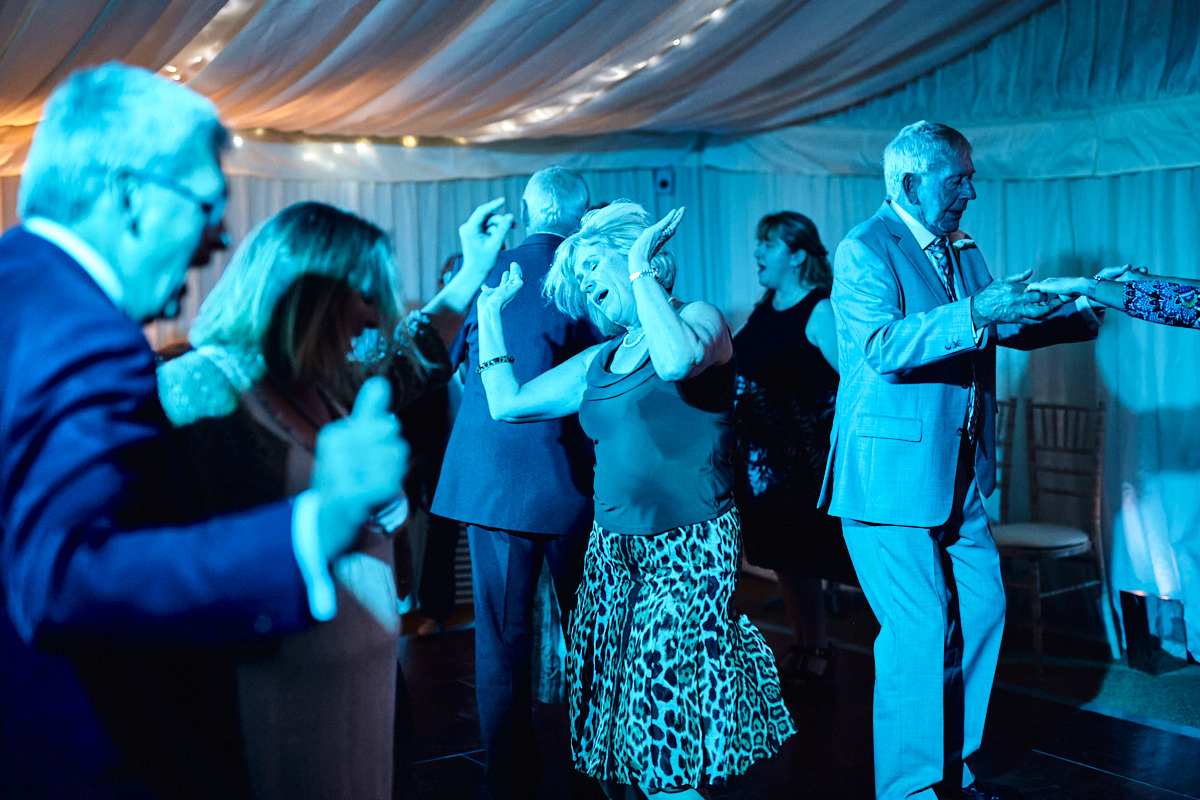 Funny wedding photo of an older guest dancing wildly