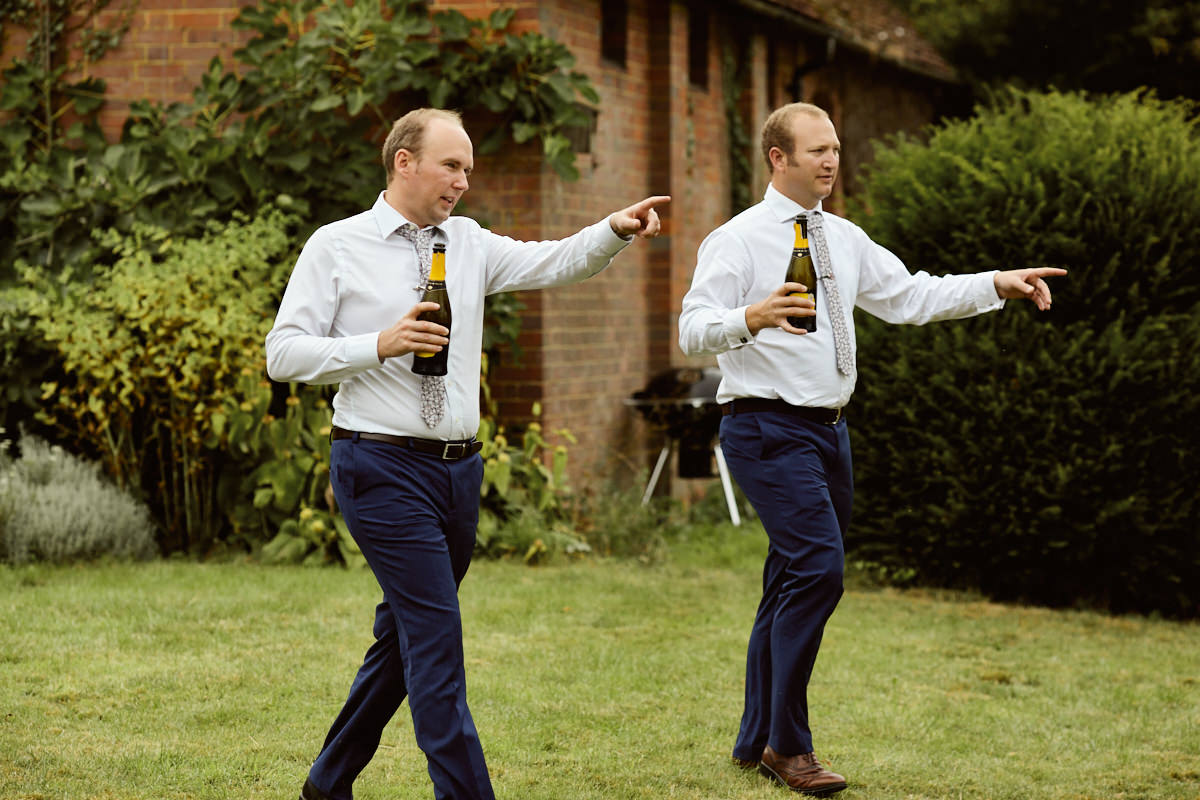 A Funny wedding photo of two guests carrying bottles of wine
