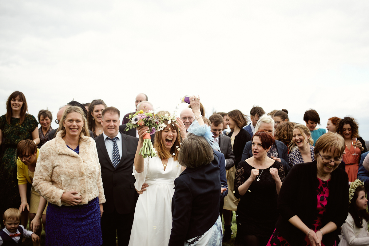 Funny wedding photo of guest pouring confetti on a bride at Barcombe Village Hall