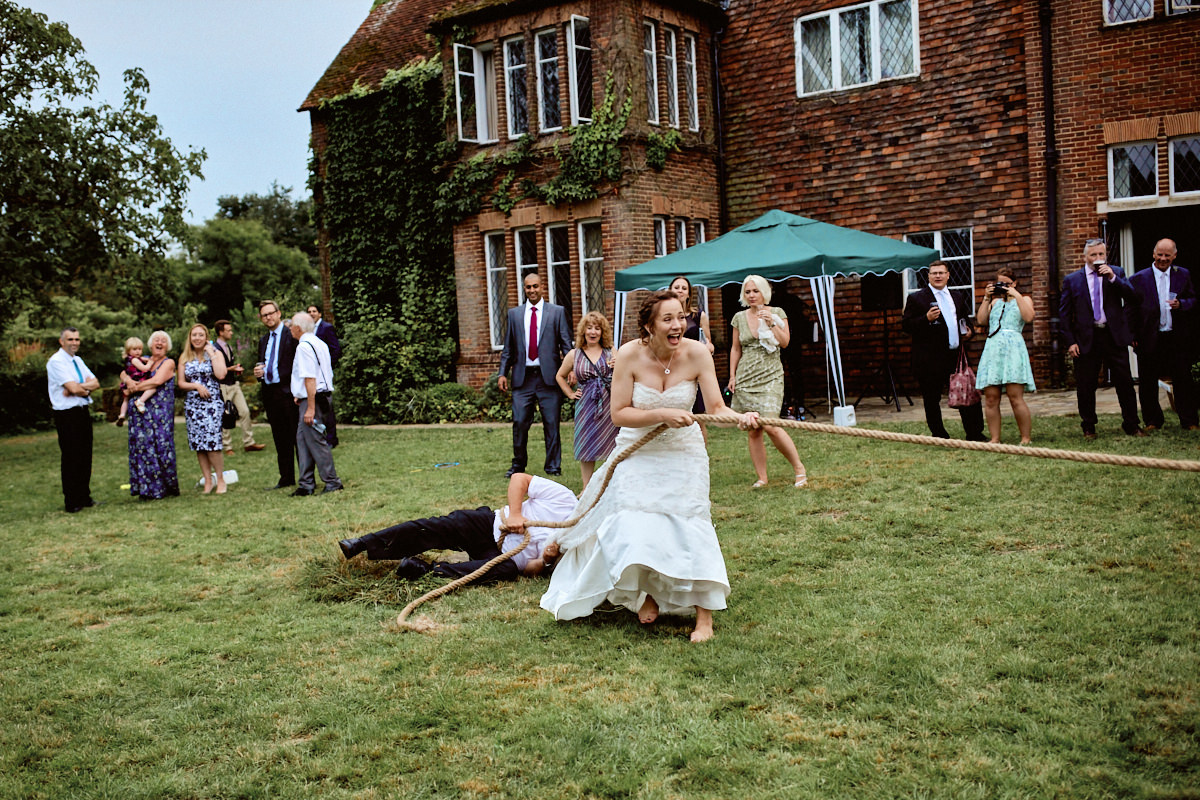 Funny wedding photo of bride in a tug-of-war game at Bore Place