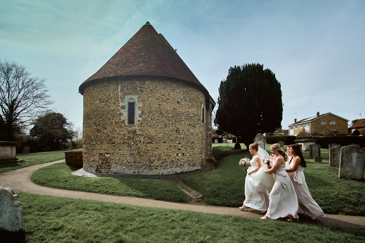Funny wedding photo of bride and bridesmaids rushing to Hertford church