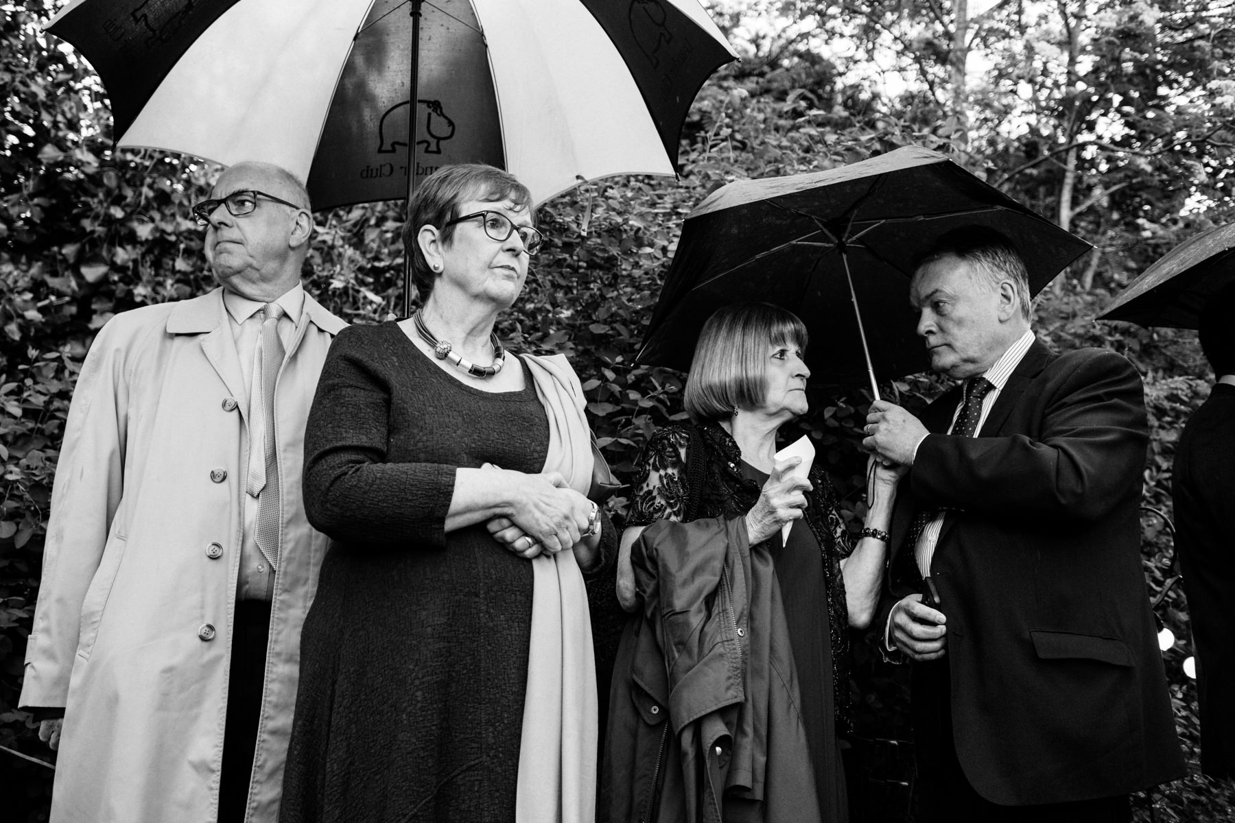 Funny wedding photo of miserable wedding guests in the rain with umbrellas