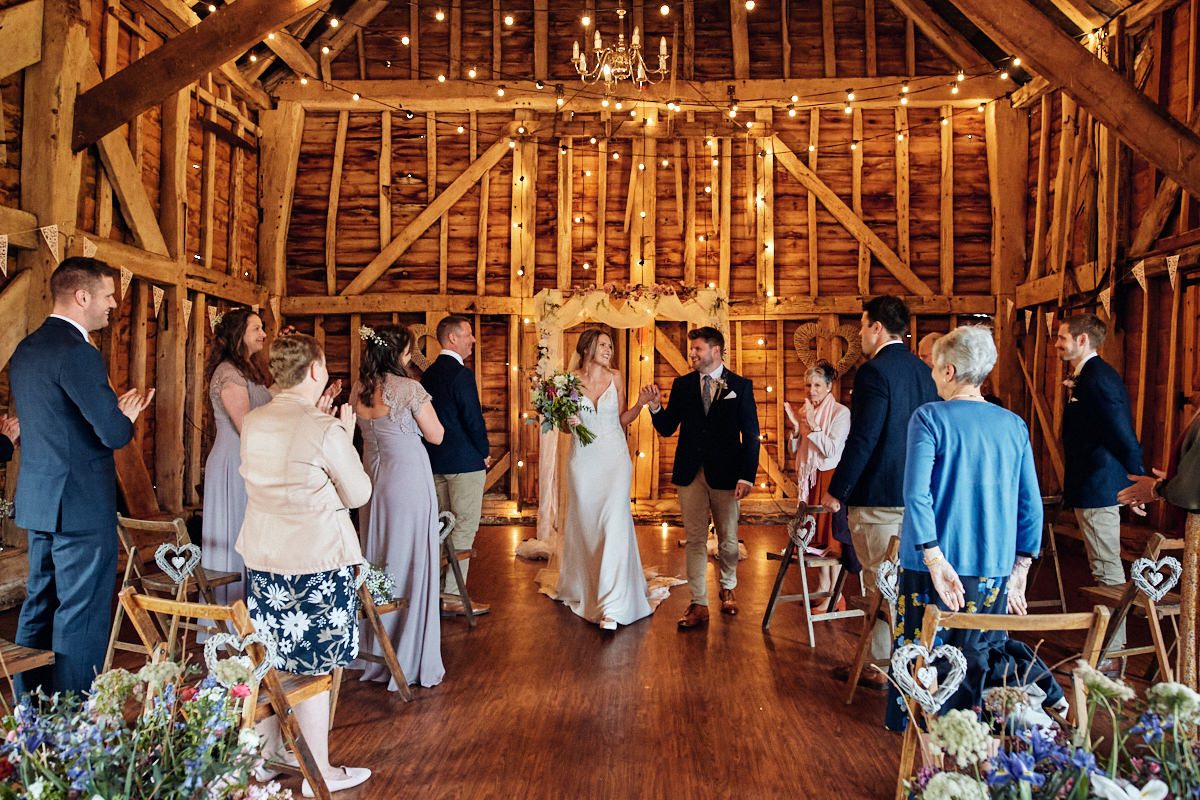 Bride and groom recessional at Great Barn in Rolvenden Kent