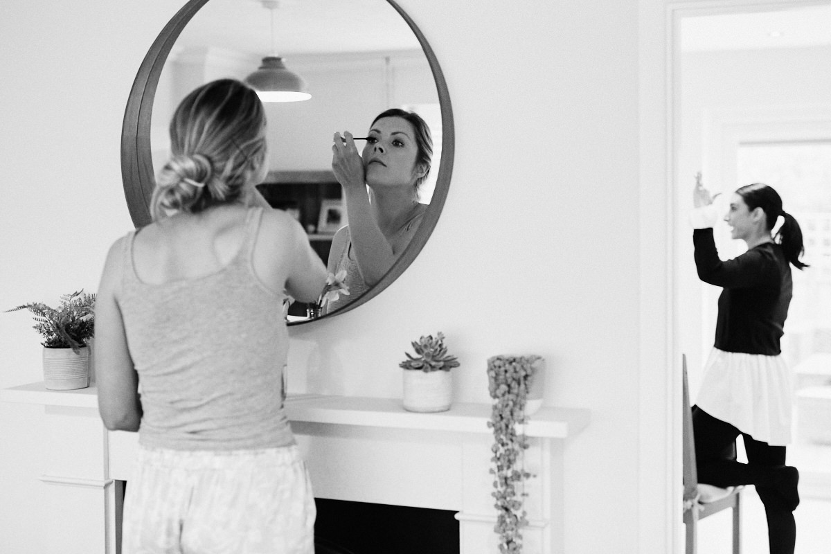 Bride applies eye make-up before wedding at Great Barn in Rolvenden Kent