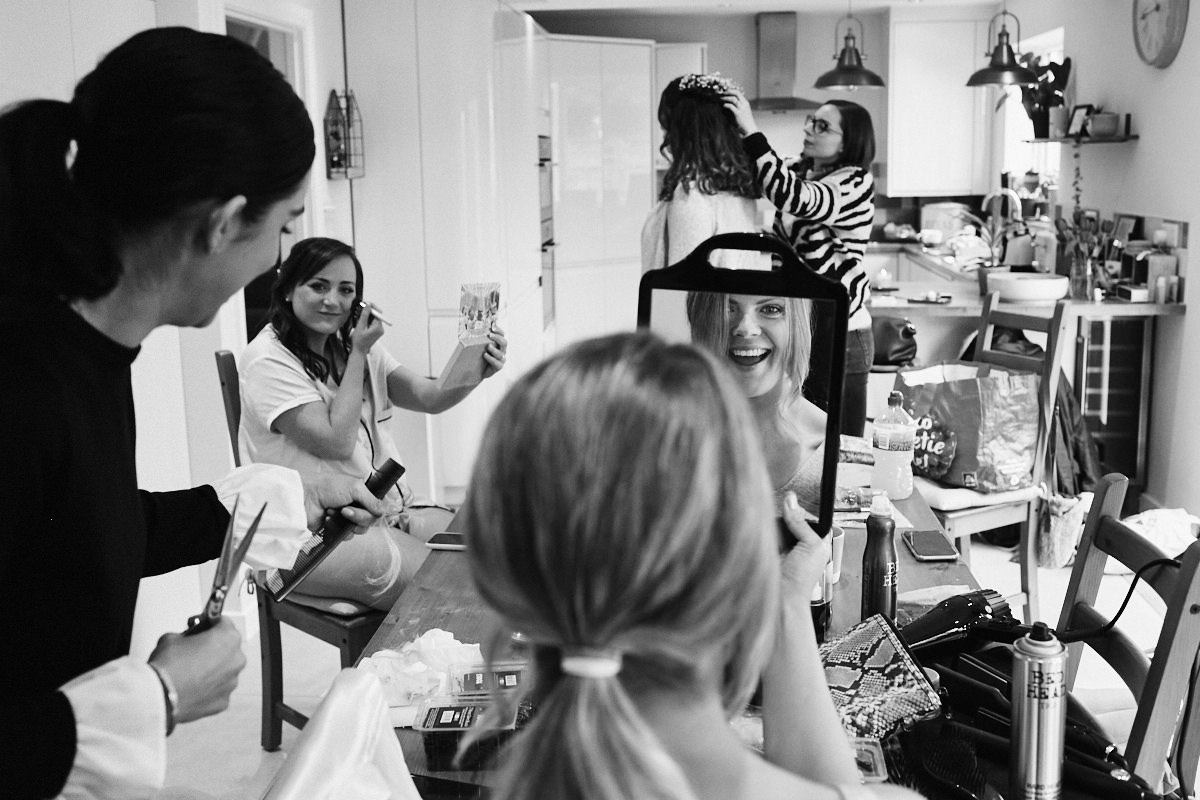 Bride gets ready with friends at home before wedding at Great Barn in Rolvenden Kent