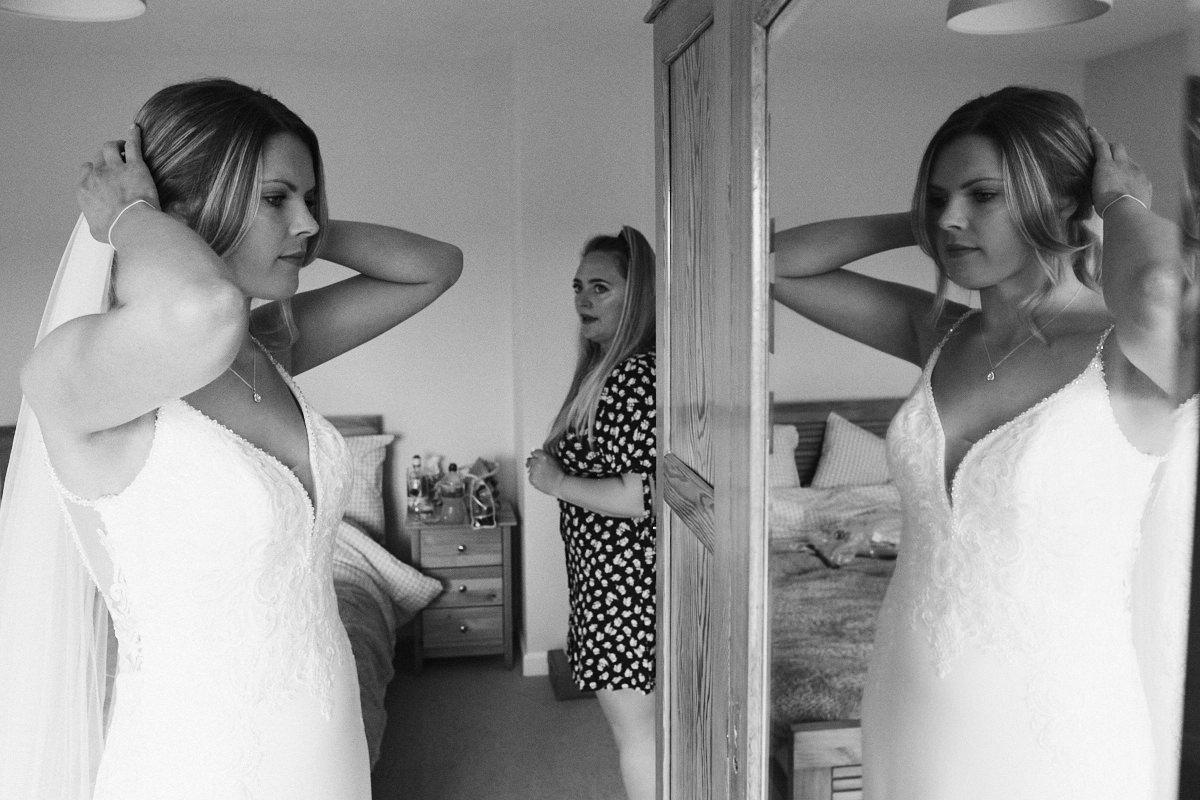 Bride adjusts hair in mirror before wedding