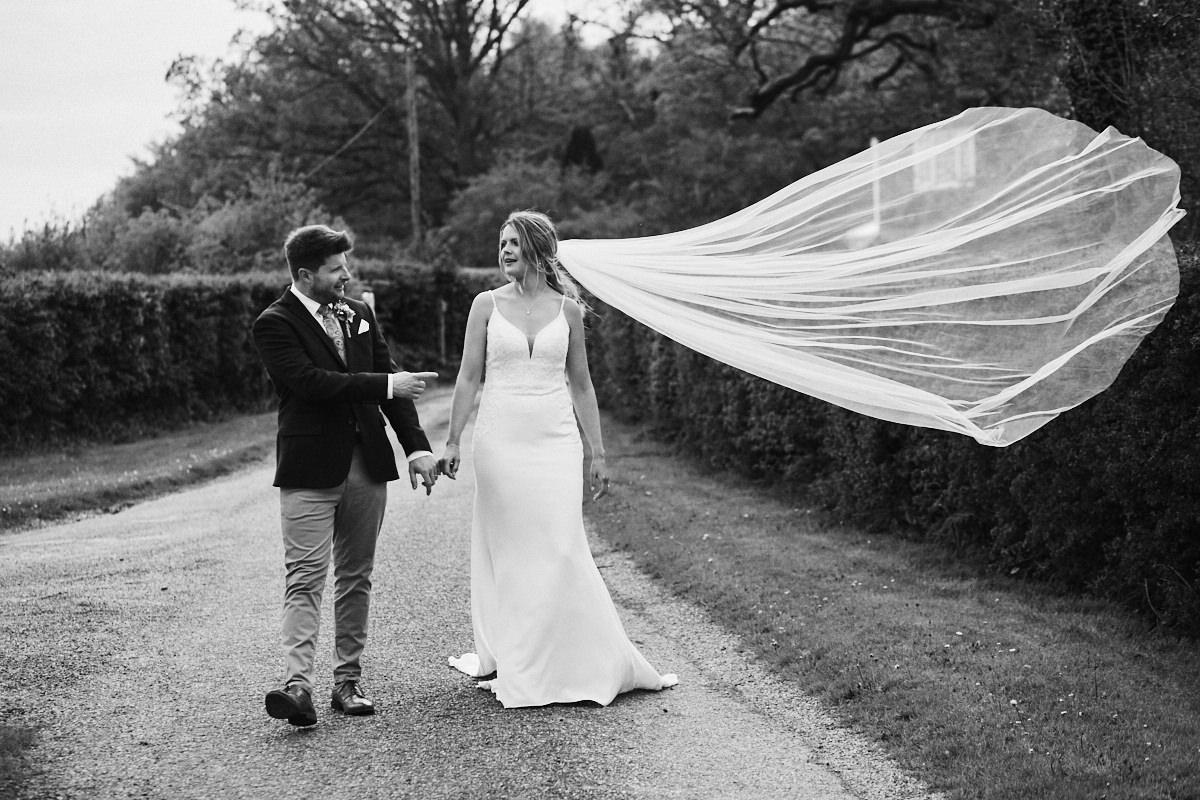 Groom points at bride's flyaway veil at Great Barn wedding