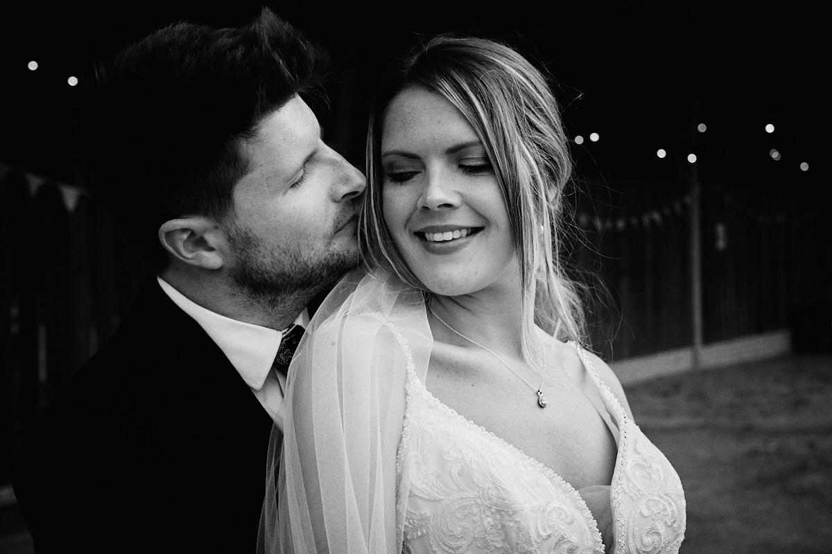 Groom kisses bride at wedding at Great Barn in Rolvenden Kent